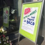 Affiche manuscrite devant la boutique pour annoncer -50% sur toute la déco avant la fête des mères